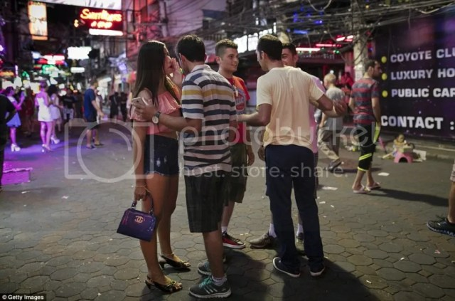 A bar girl wearing small denim shorts and a pink top was spotted speaking to a man on Walking Street in the city