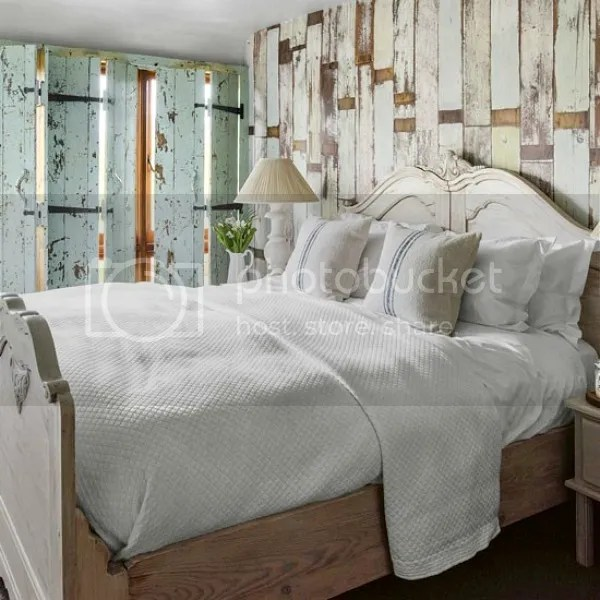 converted barn | bedroom with reclaimed floor board shutters | wallpaper behind headboard