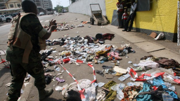 People on Tuesday stand next to clothing and various items spread over the pavement at the scene following a stampede in Abidjan.
