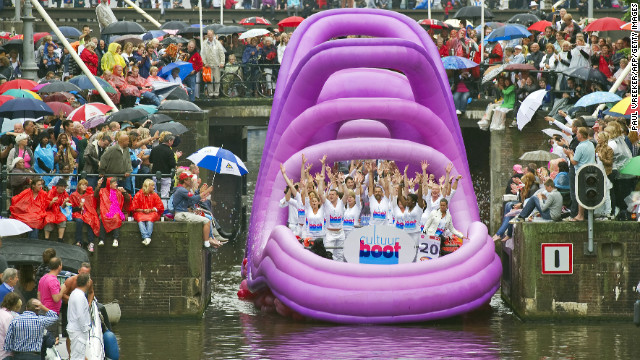 Patricipants in Amsterdam's annual Canal Pride wave to crowds.