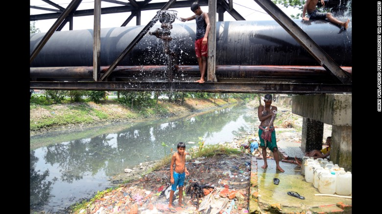 People bathe using a water pipe in Kolkata, India, on Wednesday, May 27. Stifling heat has killed more than 1,100 people in India in less than a week.
