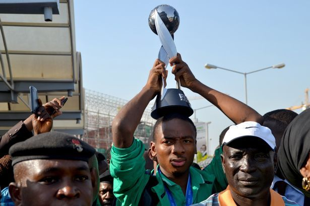Nigeria's Kelechi Nwakali carries the Fifa Under-17 World Cup trophy on his head in the midst of a crowd gathered to receive the triumphant Nigeria U17 team, the Golden Eaglets, at Nnamdi Azikiwe Airport in Abuja, on November 11, 2015