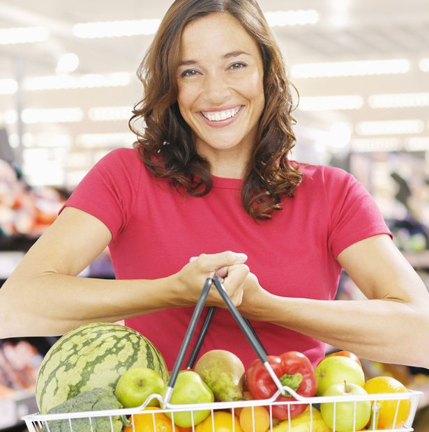 Smiling woman holding basket full of fresh fruit and vegetables