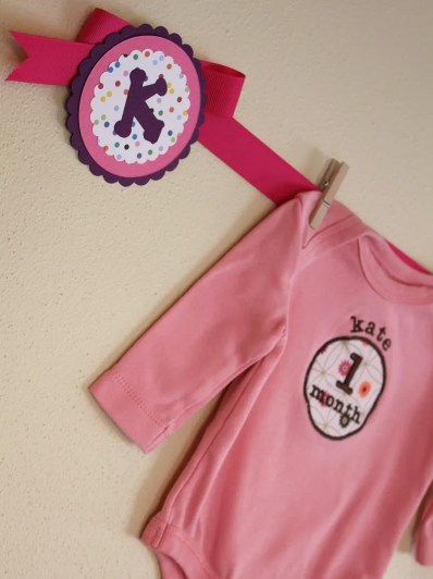 Monthly onesies wall display, first birthday party, colorful birthday party