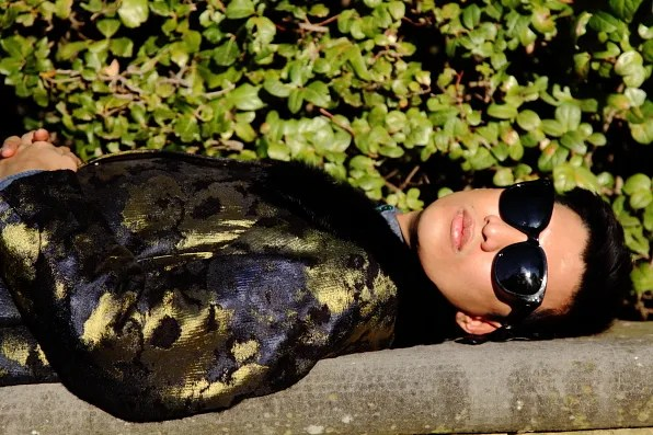 Bryanboy lying down on a bench in Antonio Marras coat at the Boboli Gardens, Florence