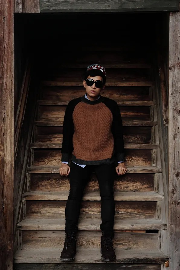 Bryanboy sitting on wooden stairs in Skansen