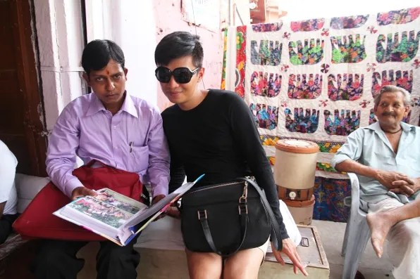 Indian man showing photos to Bryanboy