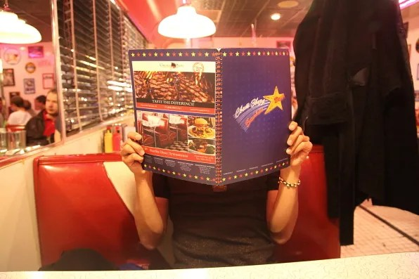Bryanboy browsing the menu at Starlite Diner, Moscow