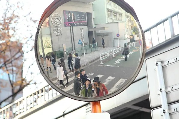 Bryanboy and Rumi in front of a street mirror in Omotesando, Tokyo