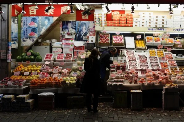 A woman buying from a fruit stall, Shinjuku Tokyo