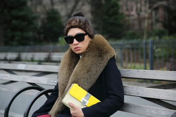 Bryanboy sitting on a bench with Rebecca Minkoff stingray clutch