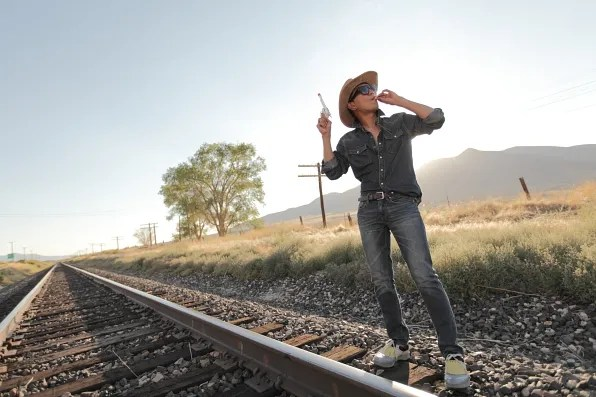 Bryanboy smoking a cigarette and holding a toy gun in Winnemucca, Nevada