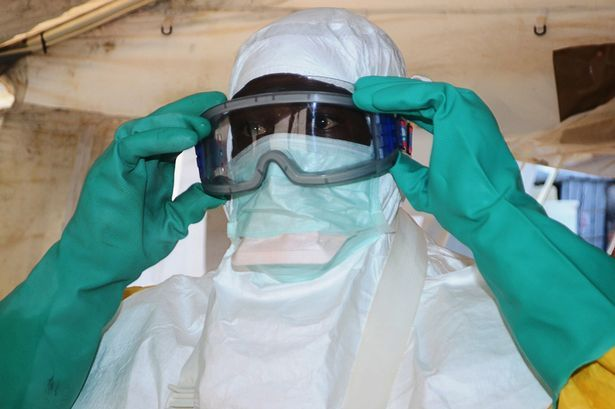Doctor putting on protective gear where people infected with the Ebola virus are being treated
