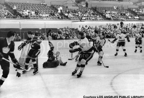 Minnesota North Stars goalie Gary Baumann sprawls awkwardly on ice at Long Beach Arena after narrowly deflecting goal attempt (arrow to puck) by Los Angeles Kings last night. Kings clicked five other times against Baumann, however, for 5-3 victory--their second in as many NHL outings on the West Coast. Photo dated: October 16, 1967.  (Milton Martinez, Herald Examiner)