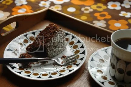 slice of chocolate sponge cake with dessicated coconut topping on vintage John Russell Black Velvet plate with coffee in matching cup & saucer