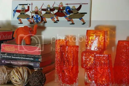 Bookshelf display with a collection of tangerine Whitefriars glass designed by Geoffrey Baxter