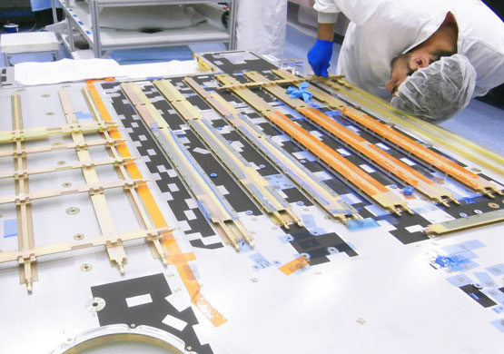 A worker during the installation of superficial Heat pipes on a thermo structural panel