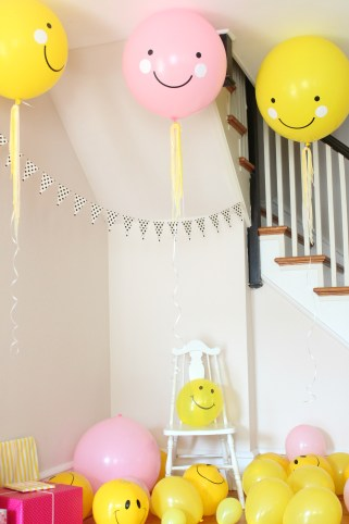 smiley face party balloons and chair
