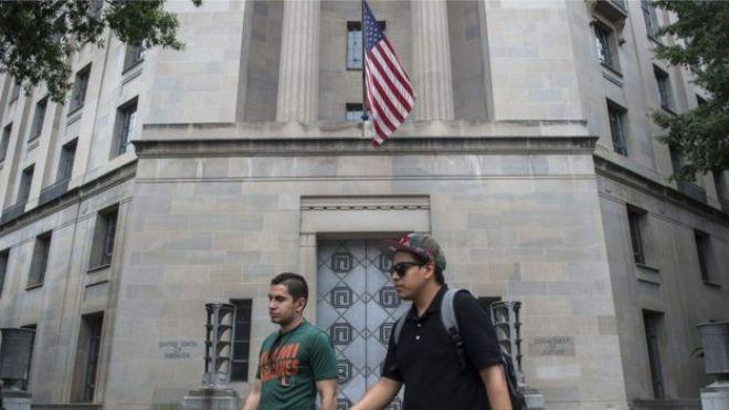 Pessoas caminham em frente ao Departamento de Justiça, em Washington