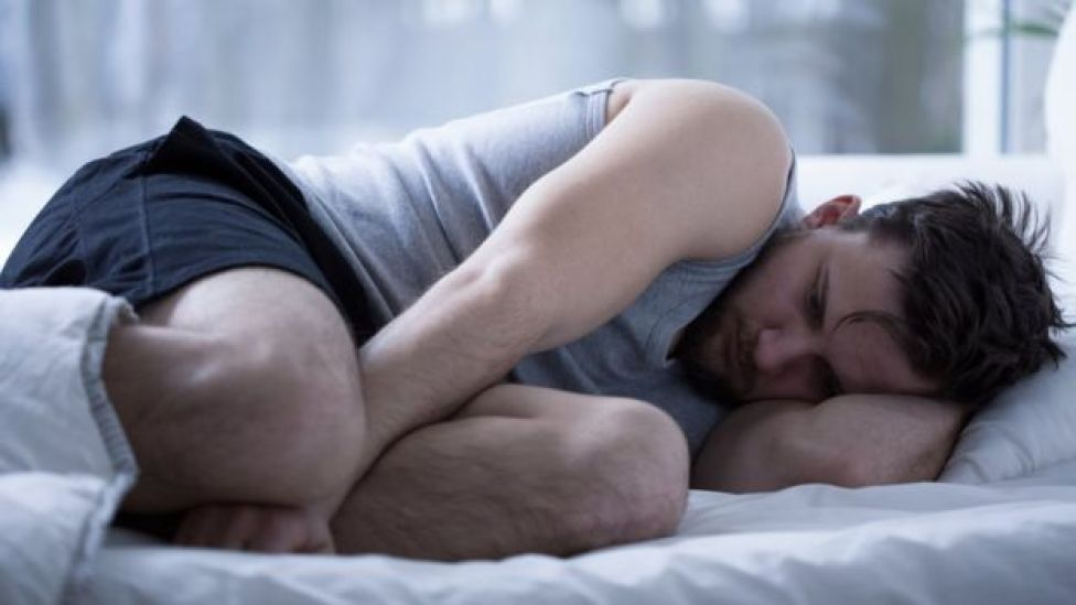 Hombre acurrucado en la cama