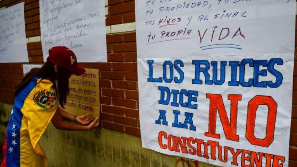 Una manifestante pega carteles contra la Constituyente.
