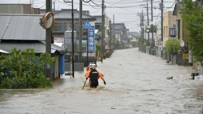 Police officers wade through a residential area flooded by the Kinugawa river in Joso, Ibaraki prefecture