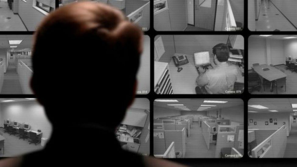 Un jefe observando a sus empleados en pantallas que captan circuito cerrado