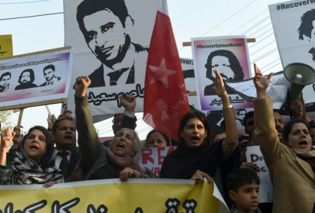 Pakistani rights activists hold pictures of disappeared bloggers during a protest in Lahore on 12 January, 2017.
