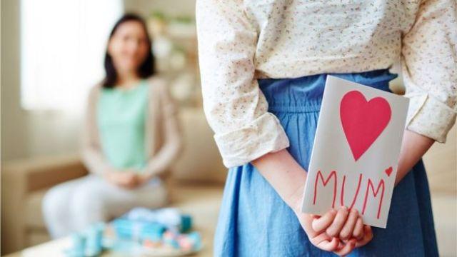 Menina com cartão de dia das mães para entregar para a mãe