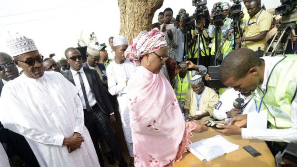 Aisha Buhari registers to vote as the president looks on