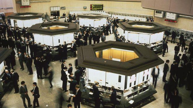 Corredores en el piso de remates de la Bolsa de Londres en 1980