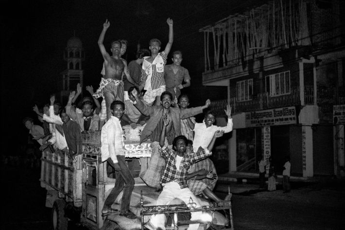 People cheering on a the back of a vehicle