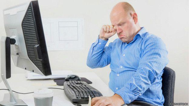 Hombre que se rasca los ojos frente a la computadora