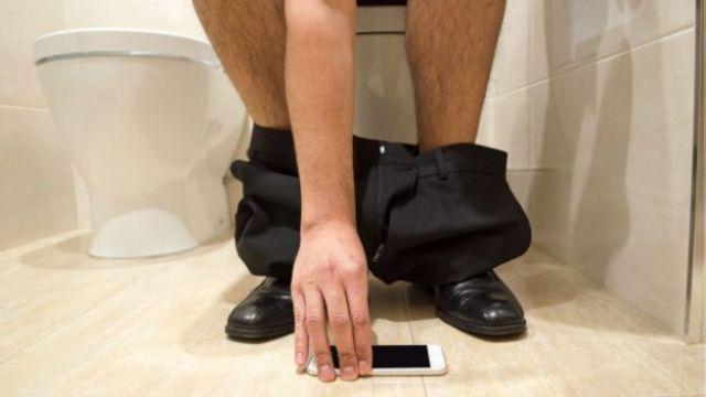 Una persona con el teléfono en el baño