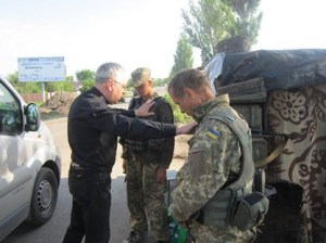 Pastor Gennadiy praying with soldiers