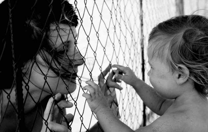 Stock Image - Mother and Child Between Bars