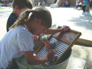 Photo/Yazmin Alvarez Children at the county museum Feb. 22 learned how to wash laundry by hand on a washboard. The activity was part of History Days -1880s.