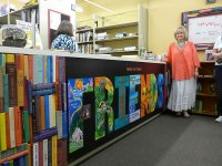 "courtesy photo/ernesto gomez   Local artist Sally Bell unveils a mural she painted for the Friends of the A.K. Smiley Public Library's bookstore March 14. The mural is a compilation of children's books and reads: ""Books are Silent Friends."""