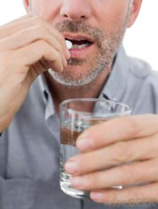 man-taking-pill-with-glass-of-water