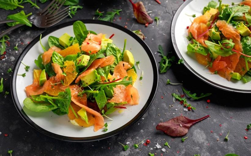 Fresh salmon salad with avocado, orange and green vegetables