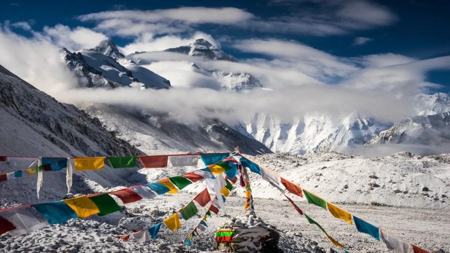 Tibetan prayer flags hang between snowy peaks