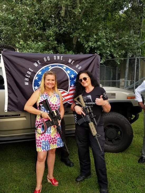 Amanda Chase poses with Q flag and Hummer
