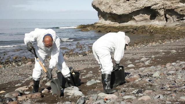 Recogida de fuel en la playa de Veneguera tras el vertido del 'Oleg Naydenov'. (ALEJANDRO RAMOS)