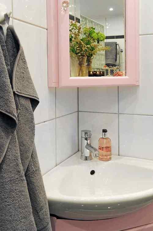 Detalle del vanitory y espejo rosas en el baño