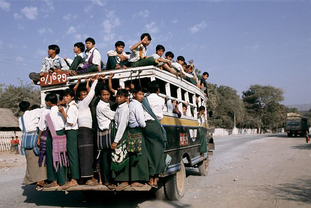 Children in white tops and green pants hang on the outside of a very crowded bus; other children sit on top of the bus