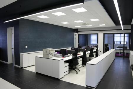 empty office with white desks and black chairs