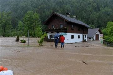 (AP Photo/Kerstin Joensson). Two residents stand on a flooded street near the Saalach river in Weissbach in the Austrian province of Salzburg, Sunday, June. 2, 2013.