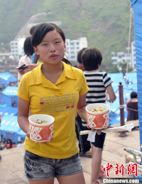 A girl returning to her relief tent with free supper.