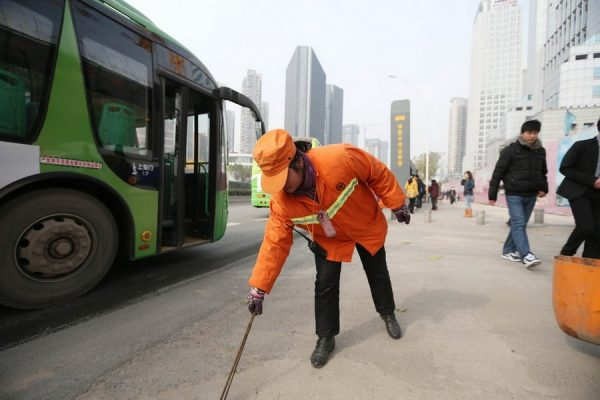 Yu Youzhen is picking up trash from the street.