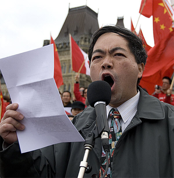 A Chinese speaker shouting into a microphone reading from a piece of paper in Canada, in protests over media bias and distortion in Canada.